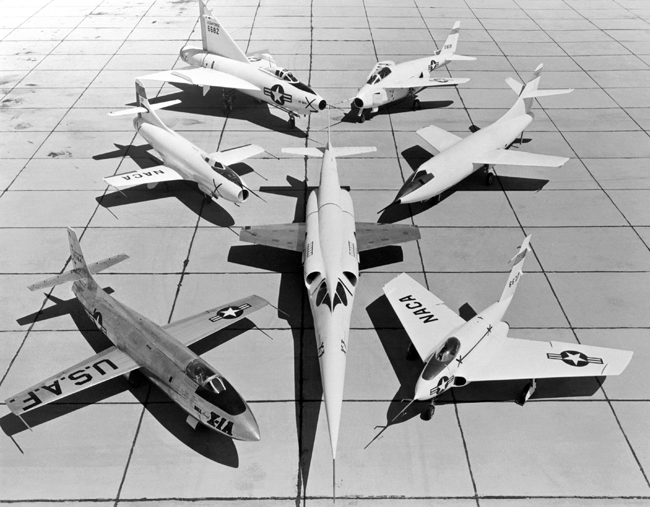 A group of U.S. experimental aircraft (X-Planes). In the center, the Douglas X-3 Stiletto; around it, clockwise from bottom left: Bell X-1A, Douglas D-558-1 Skystreak, Convair XF-92A, Bell X-5, Douglas D-558-2 Skyrocket, Northrop X-4 Bantam.